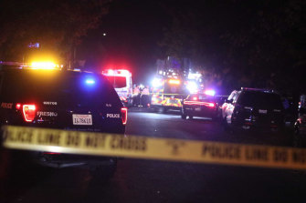 Police and emergency vehicles work at the scene of a shooting at a backyard party.