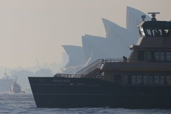 A ferry sails past the Sydney Opera House as winds blow smoke from bushfires over the CBD in Sydney.