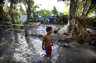 A child wades through sludge on the Island Republic of Kiribati, which often experiences inundation on high tides and is one of a number of low-lying nations exposed to the worst effects of rising waters due to climate change.