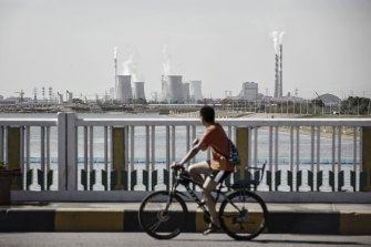 A man rides a bicycle over a bridge as power plants stand in the distance in Baotou, Inner Mongolia.