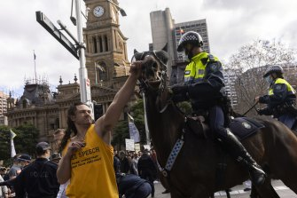 A man hits a police horse during an anti-lockdown rally in the CBD in Sydney.