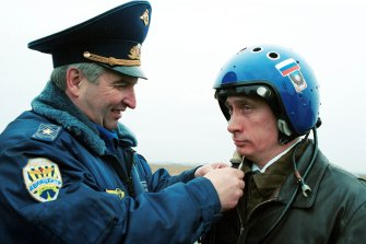 Russian air force general Alexander Kharchevsky adjusts a helmet on Vladimir Putin, then Russia's Acting President, before he flew into Chechnya in a fighter jet on March 20, 2000.