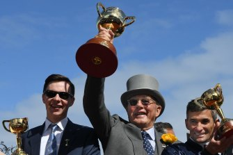 Lloyd Williams lifts his sixth Melbourne Cup after Rekindling's triumph in 2017, flanked by trainer Joseph O'Brien and jockey Corey Brown
