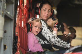 A family evacuating on board a Chinook Helicopter.