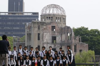 School children pose for a group photo with the Atomic Bomb Dome as a backdrop in the Hiroshima Peace Memorial Park.