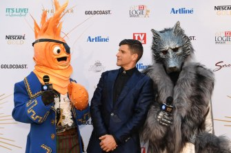 Osher Gunsberg (centre) and characters from the 'The Masked Singer' arrive at the 2019 Logie Awards.