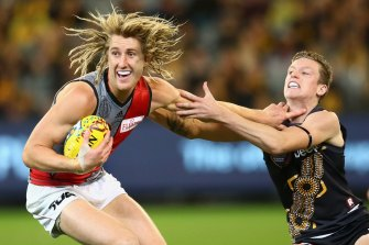 Dyson Heppell fends off a tackle by Connor Menadue in 2015.
