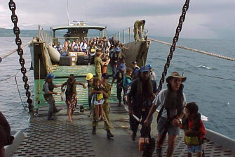 Australians and foreign nationals are assisted onto the HMAS Tobruk after being evacuated from the Solomon Islands.