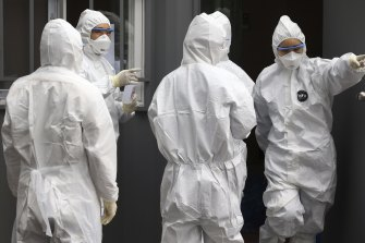 Officials wearing protective attire work to diagnose people with suspected symptoms of the new coronavirus at a hospital in Daegu, South Korea.
