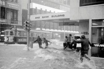 Home-bound workers brave the surging flood waters at the corner of Flinders Lane and Elizabeth Street.