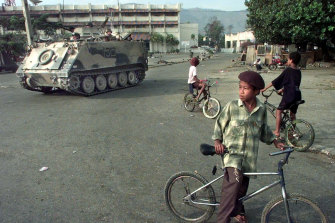 East Timorese boys ride their bicycles as an Australian armoured personnel carrier rolls down the street during a security sweep in Dili, September 1999.