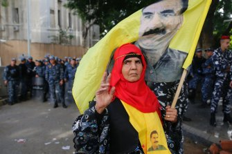 A Kurdish demonstrator holds a flag of jailed Kurdish leader Abdullah Ocalan in 2018.