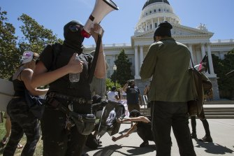 Members of the group called Antifa Sacramento try to light a flag on fire as they stage a counter-protest against skinheads at the California state Capitol in 2016.