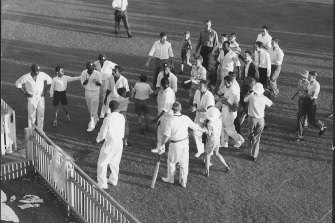 Players move to the gate leading to the dressing pavilion after the Tied Test at the Gabba.