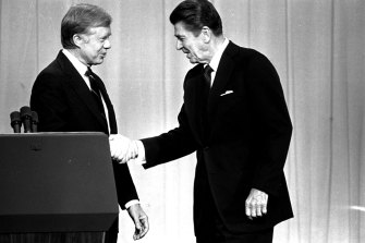 Jimmy Carter, left, and Ronald Reagan shake hands before their presidential debate in 1980.