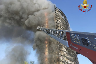 Smoke billows from a 20-storey apartment building on fire in Milan in northern Italy on Sunday.