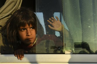 A young Syrian girl peers out the window of one of the buses bringing people to the Bardarash camp in October.