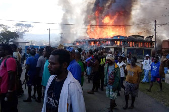 People gather as shops burn in the background during a protest in Wamena in Papua province, Indonesia, on Monday.