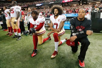 Taking a knee to make a stand: San Francisco 49ers quarterback Colin Kaepernick, centre, kneels during the playing of the US national anthem before an NFL game in 2016.