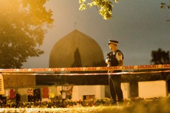 A policeman stands guard at al-Noor Mosque in Christchurch a week after the massacre in March 2019.