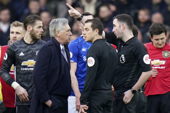 Referee Christopher Kavanagh sends Everton's manager Carlo Ancelotti off after showing him a red card.