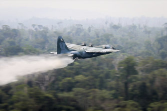 A C-130 Hercules aircraft dumps water to fight fires burning in the Amazon rainforest.