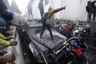 Anti-government demonstrators commandeer an armoured vehicle during a nationwide strike and protest against President Lenin Moreno in Quito, Ecuador.