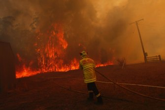 Firefighters protect property from a bushfire on Lakes Way, north of Forster near the junction of the Pacific Highway.