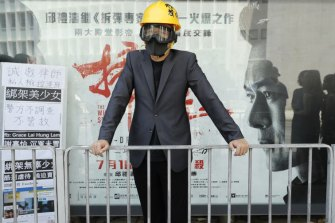 A lawyer wearing a helmet and face mask stands during a protest march in Hong Kong on Wednesday.