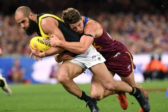 Jarrod Berry of the Lions lays a tackle on Bachar Houli of the Tigers.