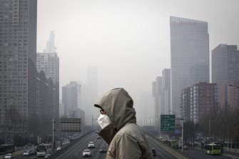 A man wearing a face mask walks on a footbridge as buildings shrouded in haze stands in the background in Beijing, China.