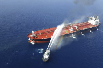 An Iranian navy ship hoses down a fire on a tanker in the Gulf of Oman on June 13.