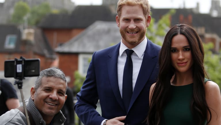 A tourist takes a selfie with the waxwork figures of Prince Harry and Meghan Markle against a backdrop of Windsor Castle.