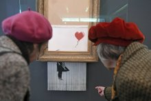 """People look at the shredded Banksy painting """"Love is in the Bin' at the Museum Frieder Burda in Baden-Baden Tuesday, Feb. 5, 2019, where the work will be shown from Feb. 5 to March 3, 2019. It was originally titled 'Girl with Balloon' and since it destroyed itself during an art auction in London, it's called 'Love is in the Bin'. (Uli Deck, DPA via AP)"""