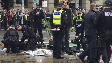 Police work to cut plastic pipes used by Extinction Rebellion climate activists to lock themselves together in Melbourne.