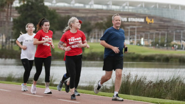 Opposition Leader Bill Shorten runs past the new Optus Stadium during a campaign stop in Perth.