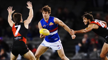 Unleashed: Essendon's Zac Clarke attempts to stop rampaging Bulldog Josh Dunkley.