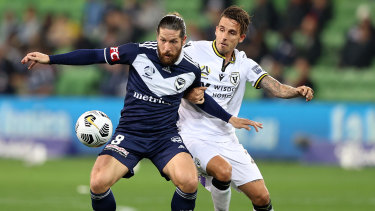 Jacob Butterfield of the Victory challenged by Matt Derbyshire of Macarthur FC during their A-League clash at AAMI Park.