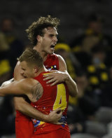 Ben King and former Tiger Brandon Ellis embrace after a goal during Gold Coast's stunning win over Richmond.