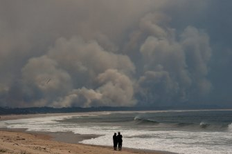 People stand on Diamond Beach watching smoke from bushfires in the Wallabi Point area fill the sky.