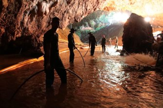 Thai rescue teams arrange water pumping system at the entrance to a flooded cave complex where the 12 boys and their soccer coach were trapped.
