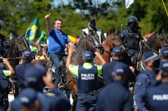 Jair Bolsonaro rides a horse during a rally in support of his presidency amid the coronavirus pandemic.