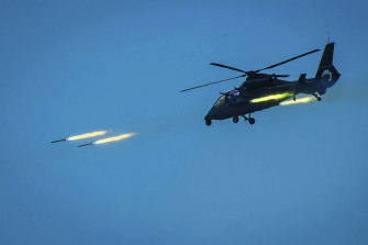 A Chinese armed helicopter fires rocket projectiles in a live-fire exercise off China's south-east coast.