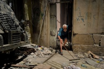 Abdulsalam Abdulqadir, 73, sweeps his porch as an air strike hits nearby in West Mosul, Iraq, in October 2017.