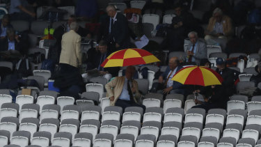 Spectators shelter under umbrellas as rain falls on day one of the 2nd Ashes Test.