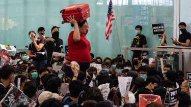 A traveller carries a suitcase on her head as she wades through sitting protesters at Hong Kong International Airport on Tuesday.