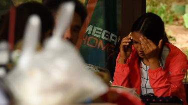 A relative reacts whilst taking a phone call at cave base camp on Saturday.