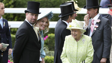 The Queen with her grandson Peter Phillips, left, and his wife Autumn in June last year.