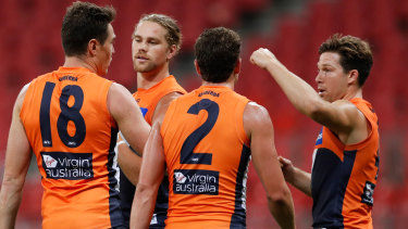 GWS players celebrate a goal.