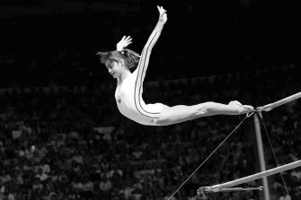 """Nadia Comaneci, of Romania, dismounts from the uneven parallel bars during a perfect """"10"""" performance at Montreal, 1976."""